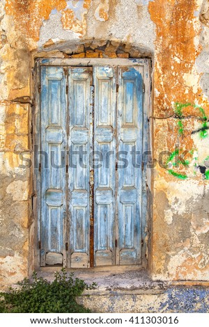 Image of a worn old house with a blue door. Sitia, Crete. - stock photo