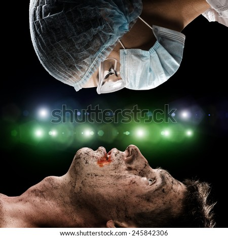 image of a wounded man and the doctor, first aid - stock photo