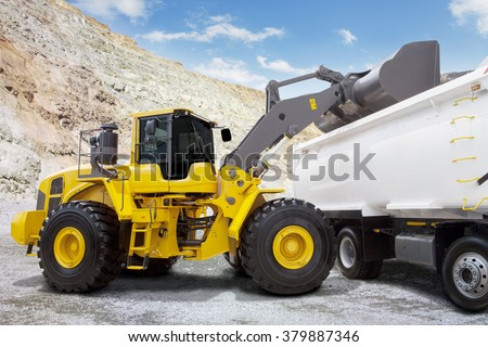 Image of a yellow backhoe loading a mine with a scoop into the truck at mining site - stock photo