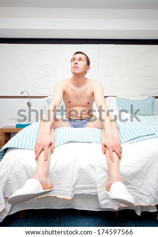 image of a young adult strange man sitting on the bed in a hotel room - stock photo
