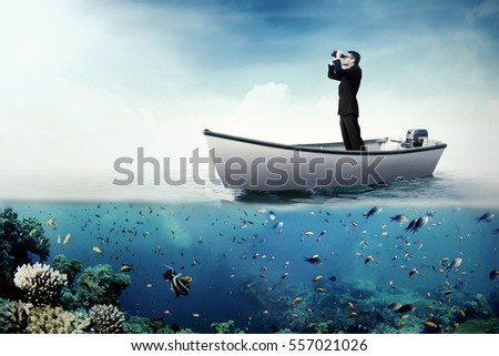 Image of a young businessman standing on the boat while looking through binoculars at the sea