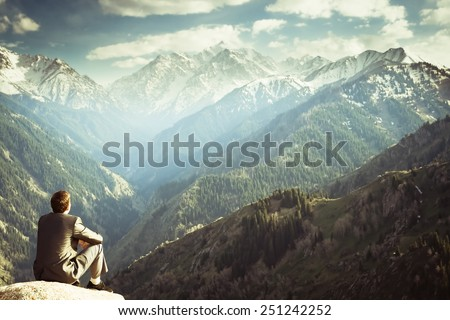 Image of a young businessman who sits on the top of the mountain and looks into the distance to the beautiful mountains, thinking about future plans. - stock photo