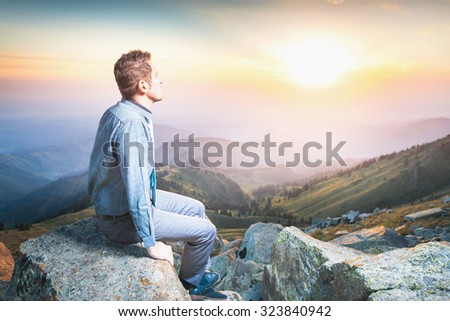 Image of a young businessman who sits on the top of the mountain and looks into the distance to the beautiful mountains, thinking about future plans