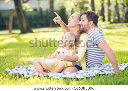 Image of a young family spending weekend in the park while a father pointing at something  - stock photo