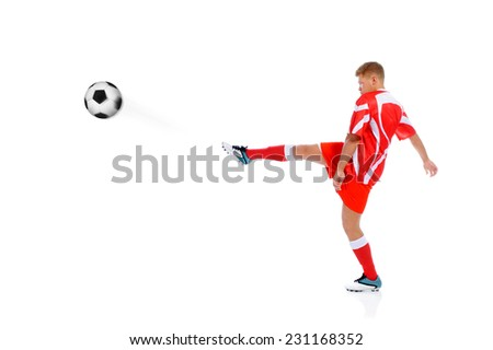 Image of a young football player with the ball in the red uniform. Isolated on white background - stock photo