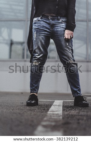 image of a young girl from the legs to the waist. It stands on the pavement in ripped jeans.shoes, sneakers, pants