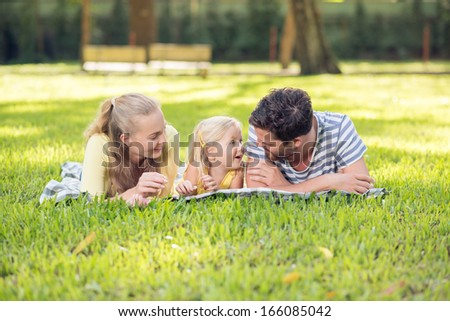 Image of a young happy family lying on the grass in the summertime - stock photo