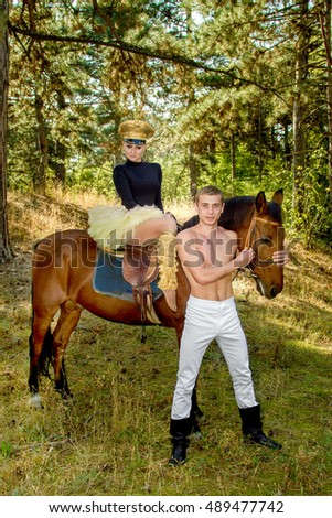 image of a young man and a girl on a horse walk in the woods