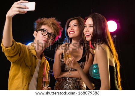 Image of a young man making a self-portrait with his friends in the club