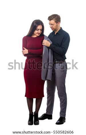 image of a young man puts his jacket on a girl in a red dress