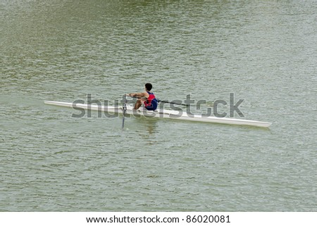 image of a young man rowing down the  Guadalquivir river in Seville, Spain - stock photo