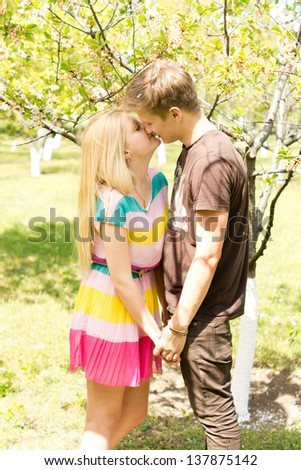 Image of a young romantic couple holding hands and kissing while on an outdoor date. - stock photo