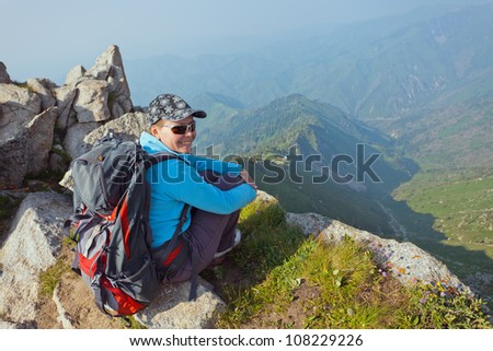 Image of a young woman - a tourist, which sits on top and looks into the camera. In the background the snowy mountain tops of the clouds. Tibet in the Himalayas. - stock photo