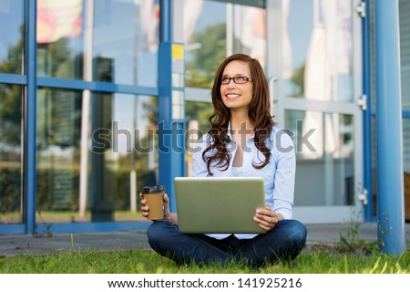 Image of a young woman smiling on something, while holding coffee and laptop, sitting crosslegged in the lawn.