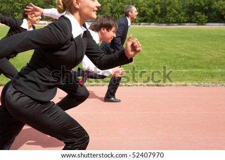 Image of active employees running down sport track - stock photo