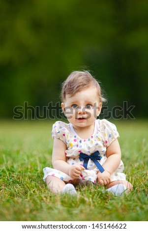 Image of adorable baby girl sitting on grass, shallow depth of field