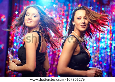 Image of adorable girls in motion enjoying themselves in the club