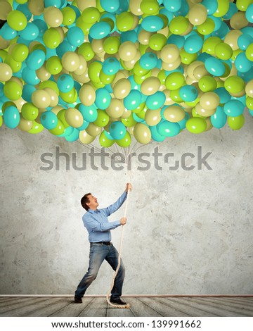 Image of adult man pulling rope with bunch of colorful balloons - stock photo