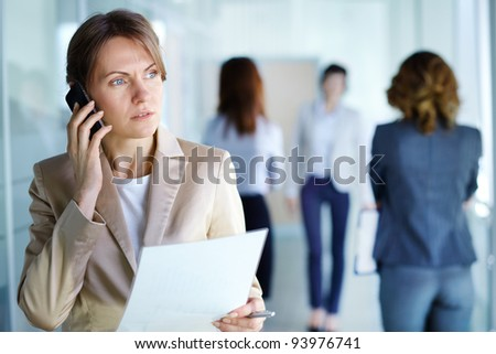 Image of agent with document speaking on the phone in working environment - stock photo