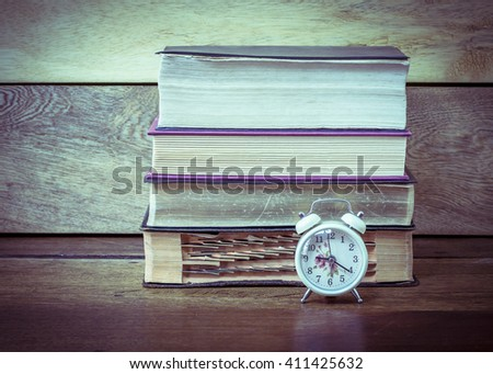 image of alarm clock with old books on wooden background, vignette - stock photo
