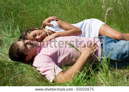 Image of amorous couple resting on green grass together - stock photo