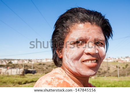 image of an african woman with dried out facial cream to protect her fair skin in the sun and symbolizes a mark of beauty - stock photo