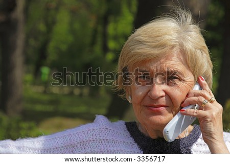 Image of an elderly woman using a mobile phone in a park.