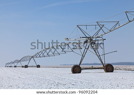 Image of an irrigation pivot in a field covered by snow in winter.