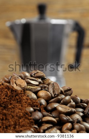 Image of an Italian Moka Express stovetop coffee maker behind coffee beans and grinds.  Shallow depth of field - focus is on top layer of beans. - stock photo