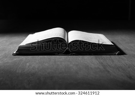 Image of an old holy bible on wooden background in dark.