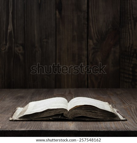 Image of an old  Holy Bible on wooden background on a wooden background in a dark space - stock photo