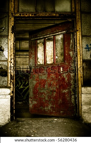 Image of an old red metal door in an abandoned factory warehouse.