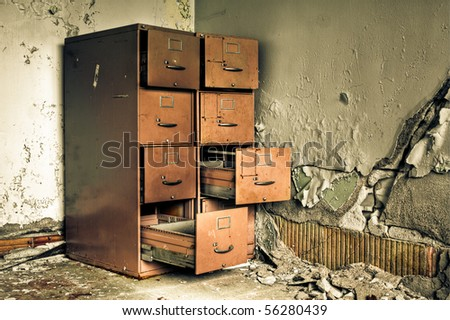 Image of an old rusty filing cabinet in a derelict abandoned building near a crumbling wall with peeling paint. - stock photo