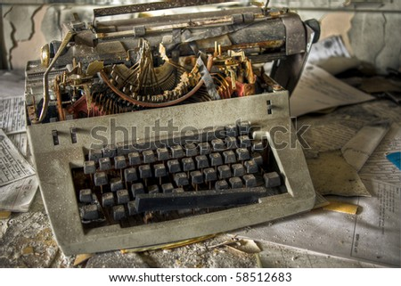 Image of an old, vintage rusty typewriter in a derelict abandoned police station covered in dust.