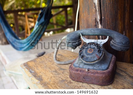 Image of an retro phone in the foreground. In the background, a hammock on a summer day in the country. - stock photo