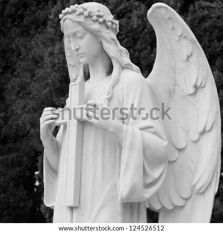 image of angel  holding a cross, detail of historic tomb on monumental cemetery in Italy, Europe - stock photo
