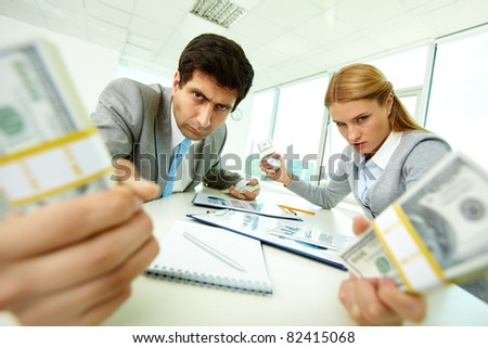 Image of angry employees with dollar bills in hands looking at you with aggression - stock photo