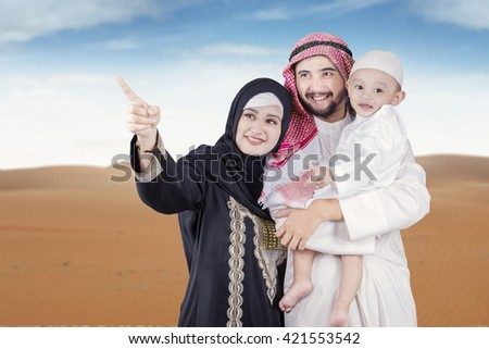 Image of Arabic woman pointing at something with her husband and son on the desert - stock photo