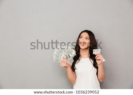Image of asian content woman 20s holding fan of money dollar banknotes and credit card and looking on copyspace isolated over gray background