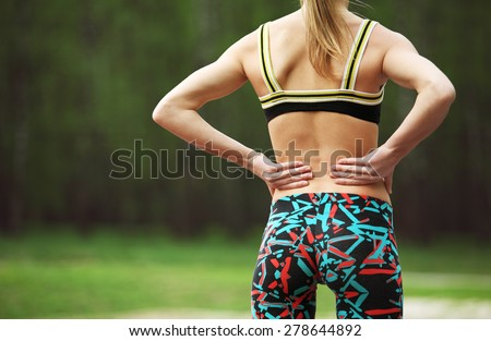 Image of athletic young woman rubbing the muscles of her lower back after jogging in park - stock photo