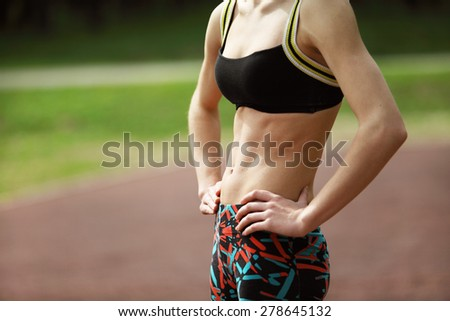 Image of athletic young woman with tight defined abs in stomach - stock photo