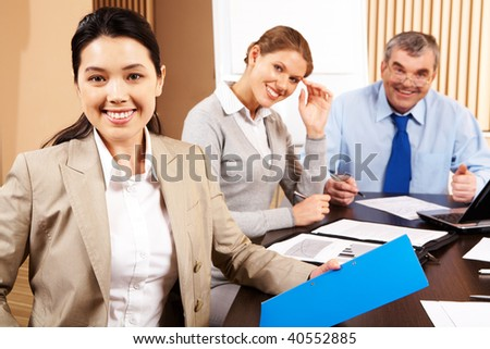 Image of attractive female on background of smart co-workers