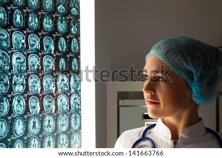 Image of attractive woman doctor looking at x-ray results - stock photo