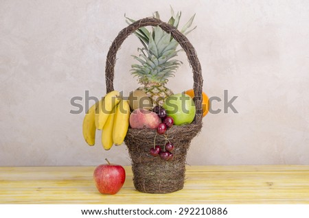 Image of basket with fruits on yellow wooden table, horizontal. - stock photo