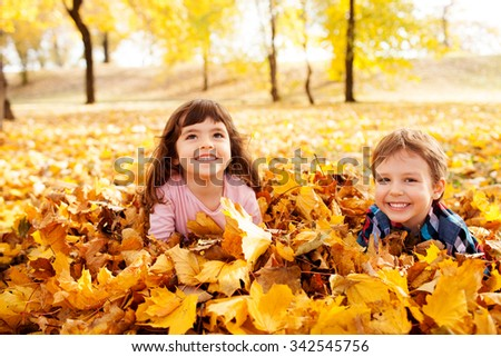 Image of beautiful boy and girl in the pile of autumn leaves, shallow depth of field