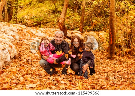 Image of beautiful female and man with cute daughter and pretty son having fun in autumnal forest, young parents with nice adorable kids playing outdoor, fall holiday, happy family concept - stock photo