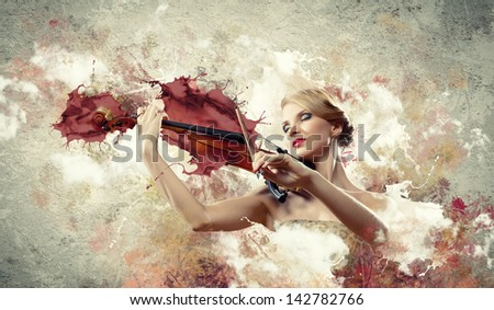 Image of beautiful female violinist playing with closed eyes against splashes background - stock photo