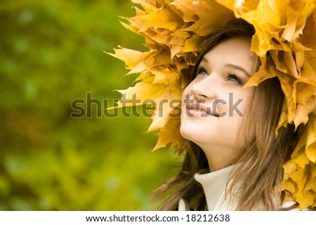 Image of beautiful girl with yellow wreath looking upwards with smile