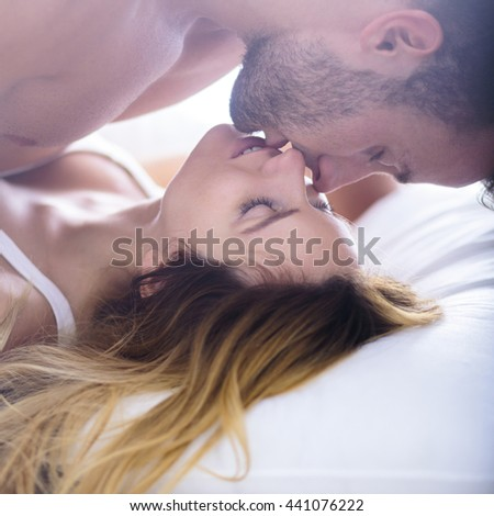 Image of beautiful woman seducing her boyfriend in bed - stock photo