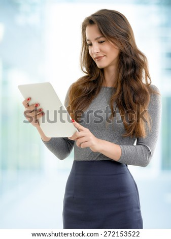 Image of beautiful young woman standing while holding digital tablet in her hands and reading text. Businesswoman working at office.  - stock photo